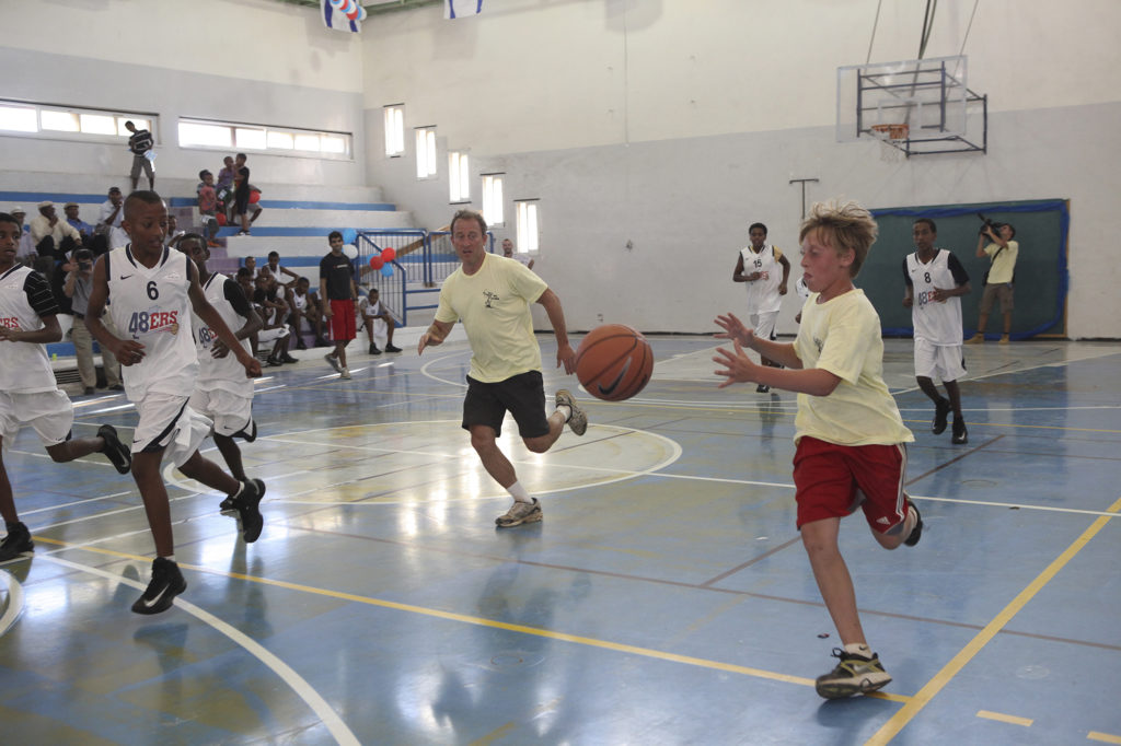 Josh Harris playing basketball with kids at a Harris Philanthropies event